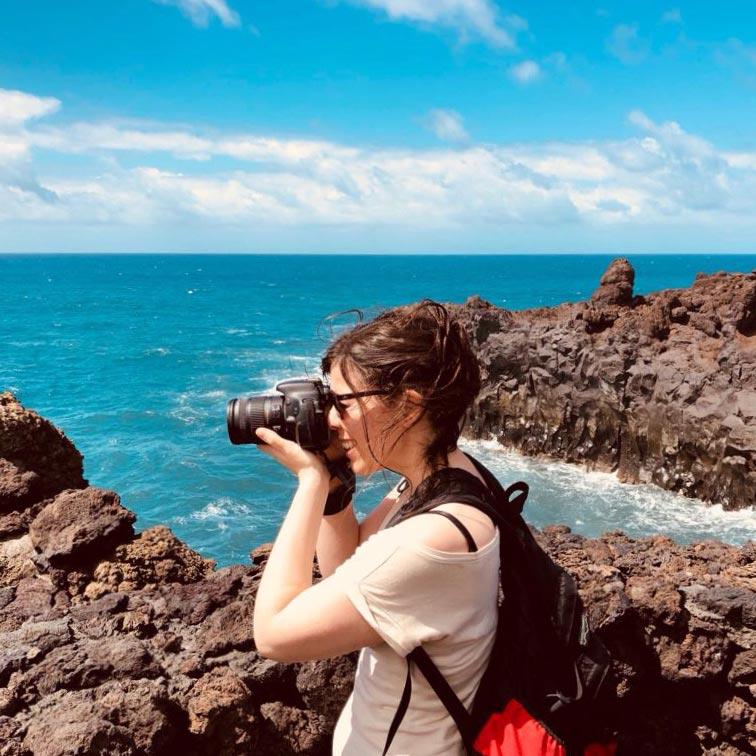 Mujer sacando una foto, de fondo se ve el mar