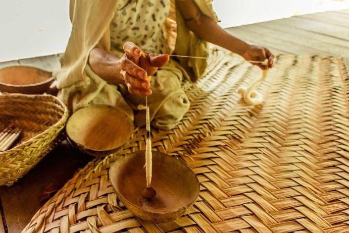 Mujer de etnima Machiguenga hilando con un huso manual