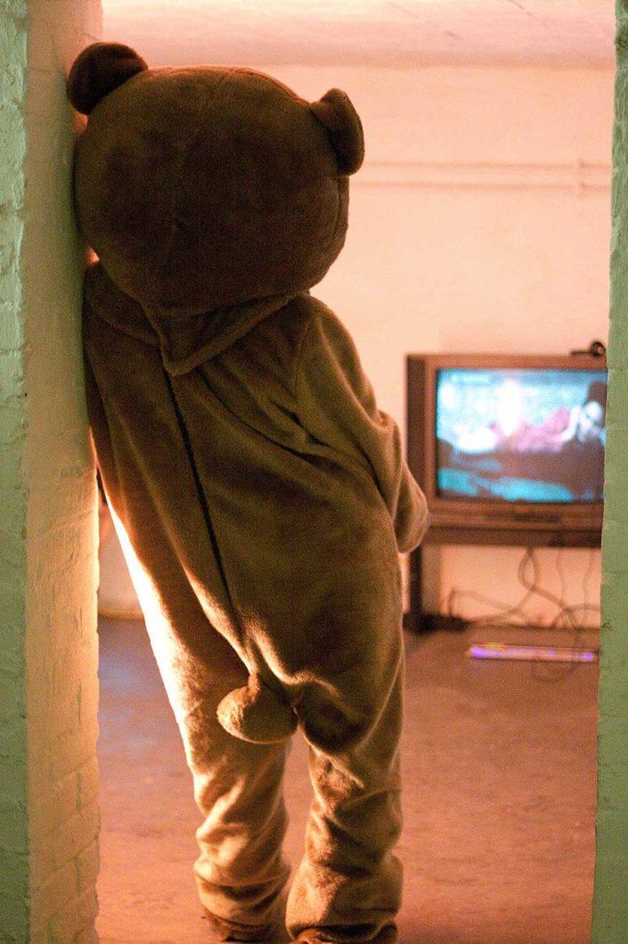 Persona disfrazada de oso mirando la televisión