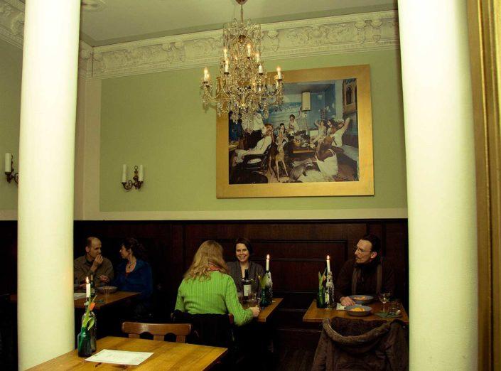 INterior de un restaurante con gente comienod en sus mesas