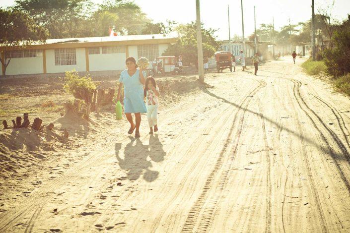 Mujer y niña andando por un camino de tierra