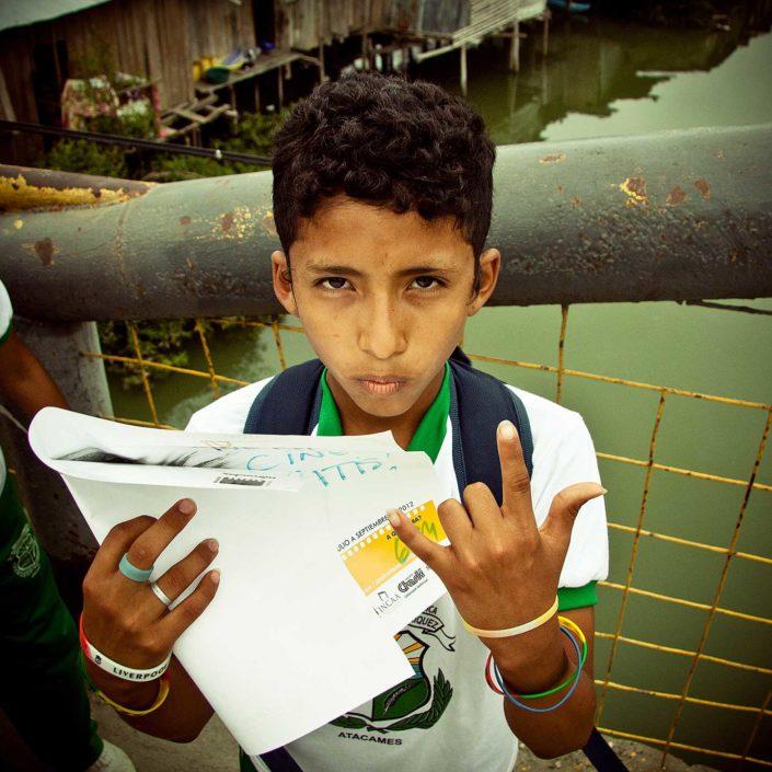 Niño con papel en la mano mirabdo a la cámaar