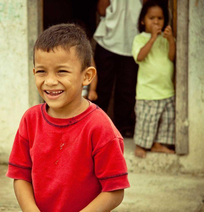 Niño sonriendo, detrás un niño sale de una puerta