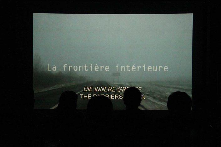 Poryección de película en la pared y siluetas de los espectadores