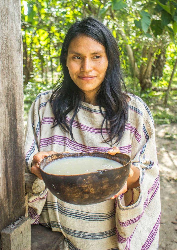 Mujer de etnia Machiguenga ofreciendo un bol de masato