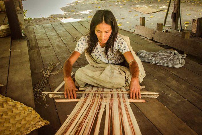 Mujer de etnia Machiguenga tejiendo en un telar manual