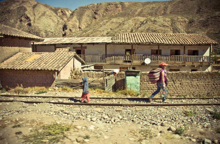 Casas, vías del tres, un niño y una mujer andando.