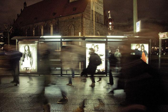 Personas pasando por delante de parada de bus conadbusting