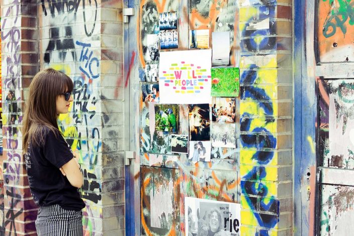 Una mujer mirando fotos colgadas en una pared