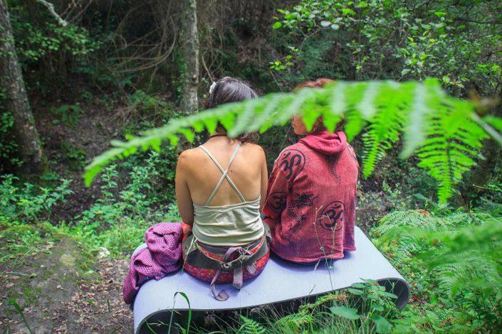 Dos mujeres sentadas en un banco en medio del bosque hablando